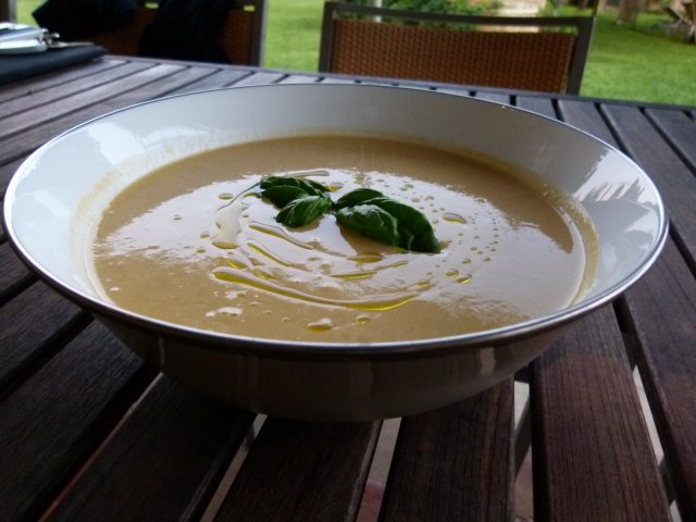 Finished serving bowl of yellow tomato soup garnished with basil oil and basil leaves