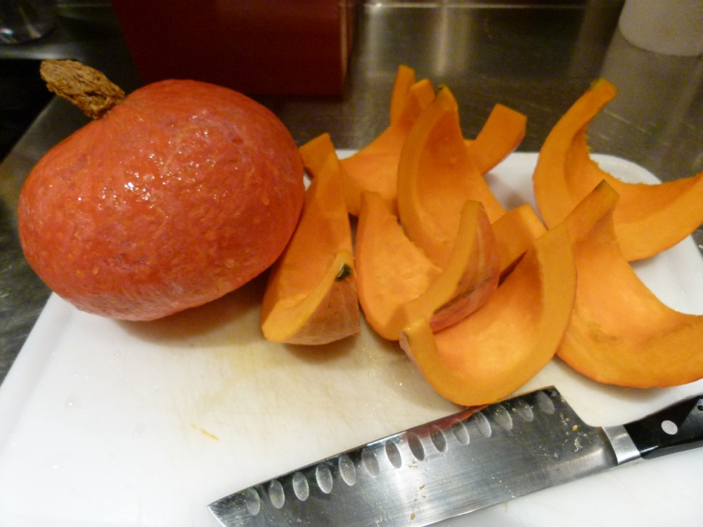 Sliced red kuri squash on a cutting board with a chef's knife