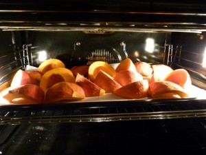 sliced red kuri squash in the oven on lined parchment paper