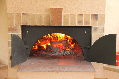 open pizza oven with burning embers and logs